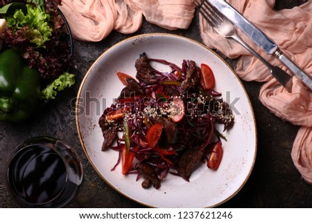 Red beet with lamb meat salad and glass of red wine