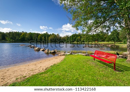Red bench at the lake in Kyrkhult, Sweden