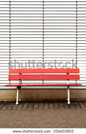 red bench in front of jalousie