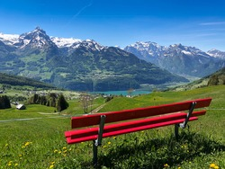 Red bench in the foreground with a view of the lake and mountains in Switzerland, blue sky