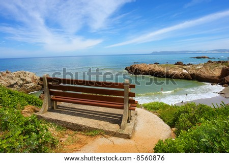 Red bench on cliff rocks next to majestic sea. Shot on Cliff Path near Hermanus, Walker Bay, Western Cape, South Africa.