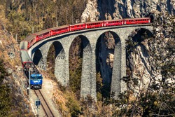 Red Bernina Express train and the Landwasser viaduct. Engadine, Switzerland, Europe