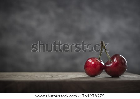 Photo of  Red berries. Ripe sweet cherries. Food that is good for the brain improves memory and skin. Retinol-rich foods. Two cherries on one branch. Object shooting. Still life in fashion style. Red on gray.