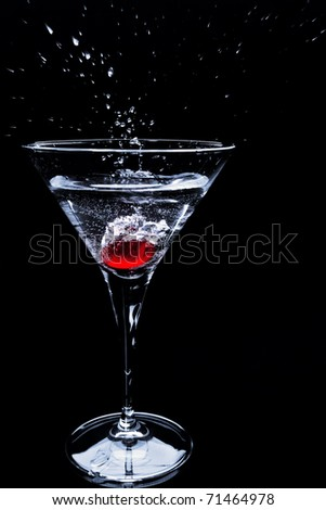Red berry dropping into cocktail with splashing over dark background