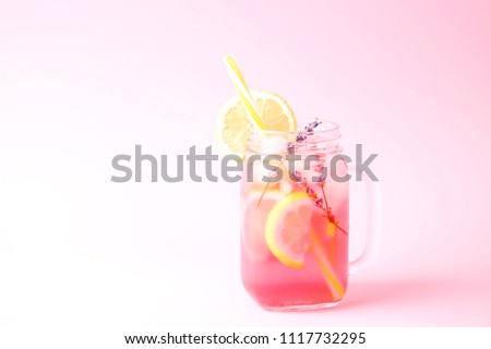 Red berry lavander lemonade, lemon and straw. Virgin strawberry mojito, non alcoholic cocktail with ice in vintage mason jar glass, Isolated on pale pink background. Copy space, top view, close up.