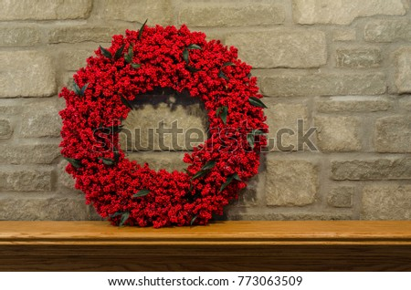 Red Berry Wreath on the left side of a gray stone fireplace's wooden oak mantel