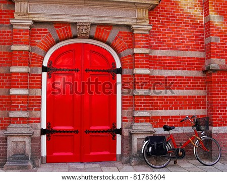 Red bicycle near a red brick wall and a red door