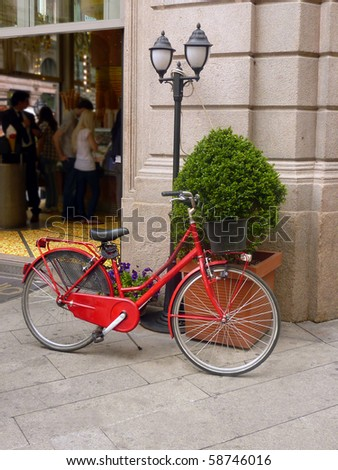 Red bicycle outside shop in Milan, Italy