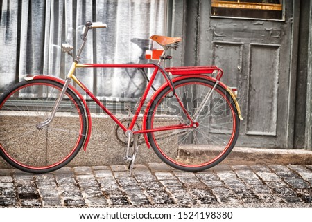 Red bicycle parked outside a townhouse door with window and drapes on a cobbled street with grunge effect