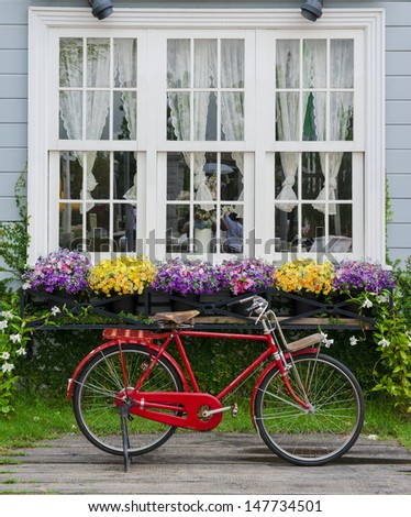 Red bicycle parked with beautiful flowers adorning the windows