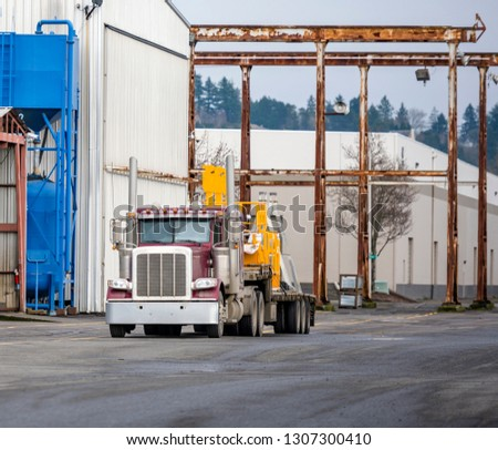 Red big rig long haul semi truck with step down semi trailer stand on warehouse parking lot waiting for unloading and possibility of continuing to the destination according to approved schedule