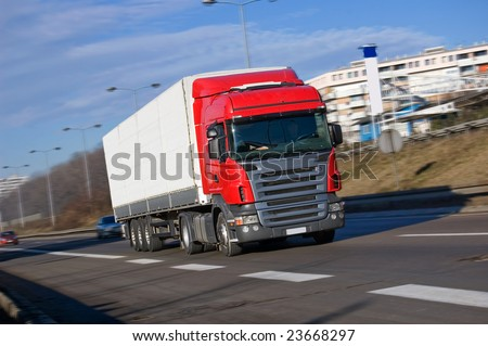 Red big truck driving fast on a high way
