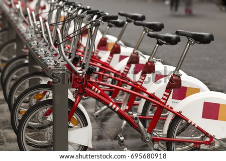 Red bikes standing in a row at bicycle-sharing system with distinctive visible saddles #695680918
