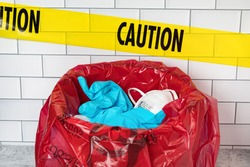 Red biohazard trash bag with used N95 respirator mask, medical exam gloves and caution tape. Concept of medical equipment shortage during Covid-19 coronavirus pandemic
