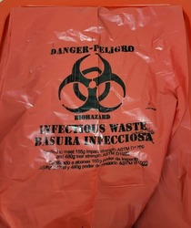 Red Biohazard waste bag with black biohazard warning symbol in hospital setting