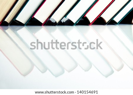 Red, black and green books in a row on white reflective surface