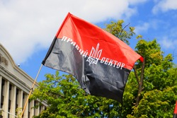 Red black patriotic Ukrainian flag with inscription in Ukrainian - Right Sector and  coat of arms of Ukraine waving. Nationalist symbol, flag of resistance. Independence, Constitution, Defender Day