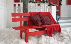 Red blanket and cushions on red bench with white artificial snow outdoors
