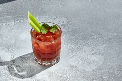 Red Bloody Mary Cocktail is a low-alcohol cocktail with vodka and tomato juice. Vintage table with sunshine and shadow. Bloody Mary or Virgin Mary Drink - vodka based cocktail garnished with celery