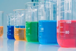 Red, blue, green, orange and dark blue color liquid medicine in the glass beaker on chemical table at the laboratory room. Chemistry and science research background.