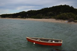 Red boat dingy in the water with beach in the back ground