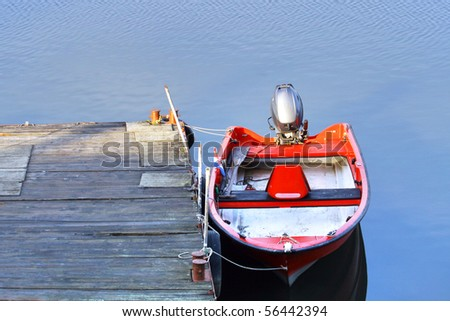 Red boat on river pier