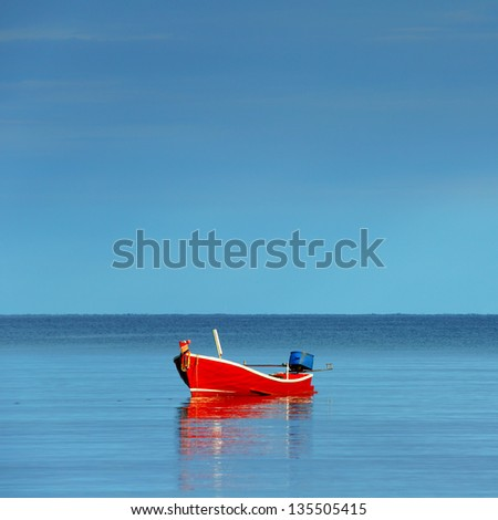 Red boat single row on sea with reflection in the water in the morning light