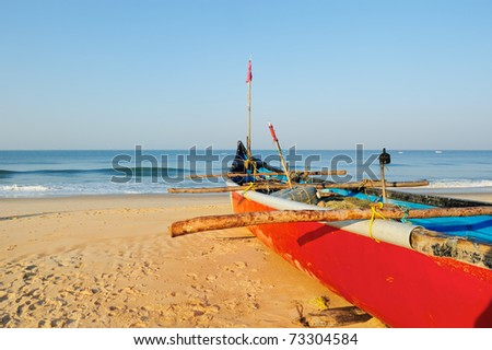 Red boat with fishing net on sandy shore