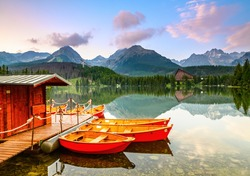 Red boats moored at wooden house on a lake with a clear  water against the background of high mountains. Strbske Pleso lake, Slovakia, Tatra mountains.