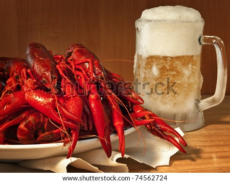 red boiled crawfishes on plate and beer - stock photo