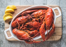 Red boiled crayfish with lemon on a cutting board.