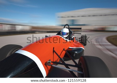 Red bolide driving at high speed in circuit.Camera on board view backward