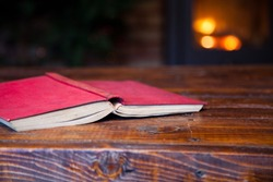 red book on wooden table - fireplace and Christmas tree in the background - cozy home concept