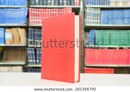 Red book standing on table with bookshelf in background