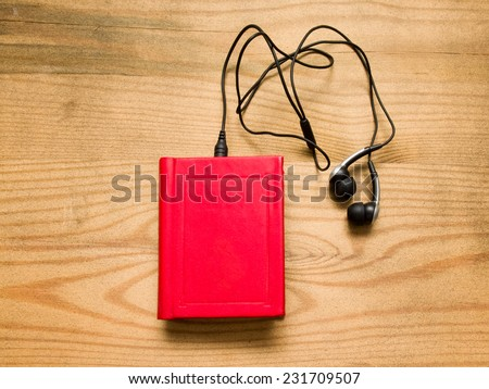 Red book with headphones over wooden background