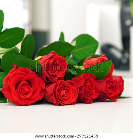 Red bouquet of roses on a white table. With eye level with copy space