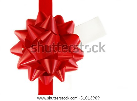Red bow and ribbon on white gift box with tag.