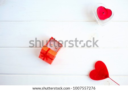 Red box with ring on a wooden white background. Valentine's Day Gift #1007557276