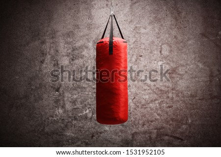 Red boxing bag hanging against gray rusty wall Stock photo ©