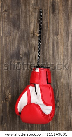 Red boxing glove hanging on wooden background