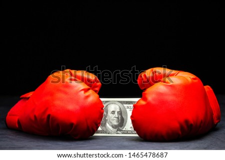 Red boxing gloves holding the dollar banknote on cement floor in darkness. Concept of fighting for money or business battles.