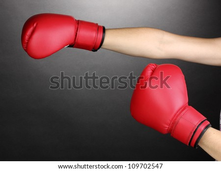 Red boxing gloves on hands on grey background