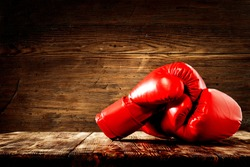 Red boxing gloves on wooden top background.