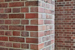 Red brick and brick edge from pillar in front of wall as texture background