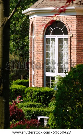 Red brick bay window of an upscale home amid garden plantings