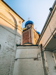 red brick building, church with a dove dome and a cross between white carp walls, sunny, summer, autumn, sunset, blue sky