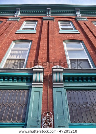 Red brick building with attractive architectural accents in aqua green.