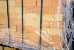 Red brick covered with packaging film on pallets in a warehouse of building materials.