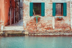 Red brick facade of an old building with emerald green windows, situated in front of the Channel in Venice.