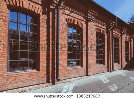Red brick facade with large windows, office premises equipped in a former industrial building, loft style